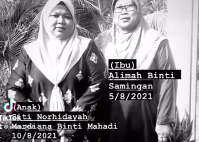 Siti Norhidayah Mardiana Mahadi stands next to her mother Alimah Samingan. Both wear baju kurung and head scarves. Both are plump with round faces. Alimah wears glasses.