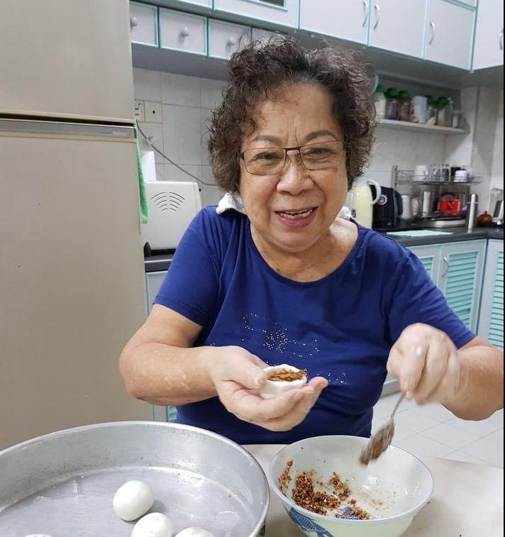 Teo Lan Kim poses with a smile while preparing food