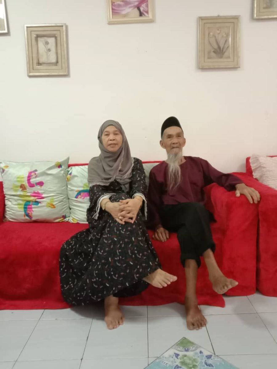 Talib Omar and his daughter sit on a red couch. Talib has a long grey beard. He wears a songkok, a maroon baju melayu and black trousers..