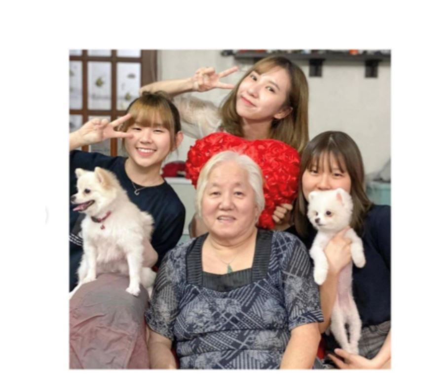 Tan Hock Soon surrounded by her granddaughters, who are holding puppies. Tan Hock Soon has a head of white hair and wears a necklace with a jade pendant.