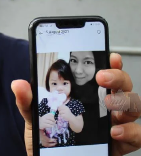 Nur Shahirah Azlan's husband holds up his phone, showing a picture of Nur Shahirah with their toddler daughter. Nur Shahirah is a young woman. She wears a headscarf.