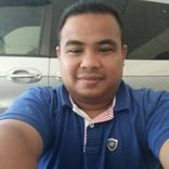Bob Pendek @ Syariman Dragster takes a selfie in front of a vehicle. He is wearing a collared T Shirt.