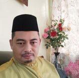 Mohd Nezam in a selfie. He is wearing baju melayu and songkok. He has a mustache and goatee.