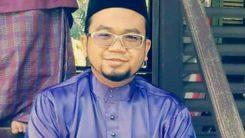 Shaiful Hazmeer Jakariah poses in a baju melayu and songkok. He wears glasses and has a goatee.
