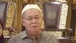 Annuar bin Hussin poses in from of a royal throne. He wears a white kopiah, a button down shirt and a sling bag