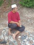 Abdul Razak Jusoh sits on a pile of rocks. He is barefooted and wear a white kopiah, a red T-shirt and rolled up gret pants.