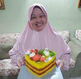 Norhayati Tajuddin smiles as she holds a pulut kuning cake.