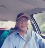 Redzuan Manan in the driver's seat of a car. He is wearing a cap and a button down shirt. He has a grey goatee.