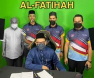 Ramli bin Ibrahim stads next to three colleagues, behind another collague who is sat. He is wearing a face mask.