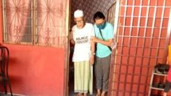 Misnon Ramli is assisted by his son out of the home. He is wearing a kopiah T-shit and sarong. The photo was taken before they left for the clinic, and minutes before he died en route.