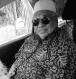 Mohd Saidi bin Mahat poses in a car. He is wearing aviator sunglasses with a white kopiah and a batik short sleeved shirt