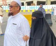 Nik Ruhani binti Nik Mah walking with her husband in Mecca. She is holding his arm. She wears a black arbaya, and a niqab.