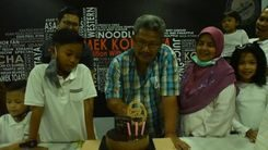Md Yusop Talib cuts his birthday cake while surrounded by his family.