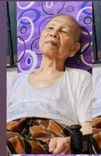 Song Sang bin Bujal is an elderly man. He wears a white undershirt and sarong, while sitting on a lazy chair.