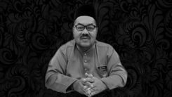 Md Noh bin Yusoff wears a songkok and baju melayu. He wears dark rimmed glasses and has a mustache.