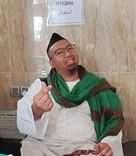Nabil Azwar wears a half-rimmed glasses, a kopiah and jubah, and has a scarf around his shoulders. He is smiling and has a goatee. He gestures the 'mini love' sign wit his fingers.