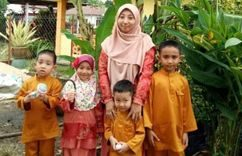 Fatimah Mohd Nawi with her children, a girl and three boys. They are wearing baju kurung and baju melayu.