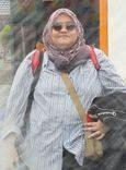 Asny Haniz wears a sunglasses, a headscarf, a striped button down shirt, a backpack and a sling bag. She holds a jacket.